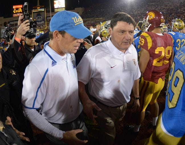 Nov 30, 2013; Los Angeles, CA, USA; UCLA Bruins coach Jim Mora (left) and Southern California Trojans coach Ed Orgeron shake hands after the game at Los Angeles Memorial Coliseum. Mandatory Credit: Kirby Lee-USA TODAY Sports