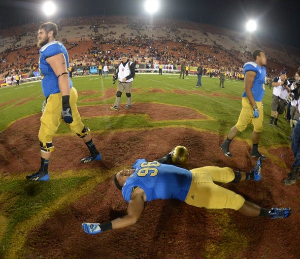 Nov 30, 2013; Los Angeles, CA, USA; UCLA Bruins defensive tackle Eli Ankou (96) celebrates on the Southern California Trojans logo at the end of the game at Los Angeles Memorial Coliseum. Mandatory Credit: Kirby Lee-USA TODAY Sports