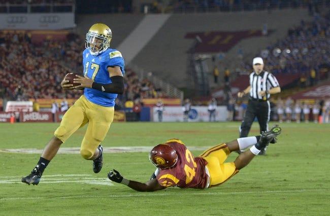 Nov 30, 2013; Los Angeles, CA, USA; UCLA Bruins quarterback Brett Hundley (17) eludes Southern California Trojans linebacker Devon Kenard (42) to score on a 4-yard touchdown run in the third quarter at Los Angeles Memorial Coliseum. Mandatory Credit: Kirby Lee-USA TODAY Sports