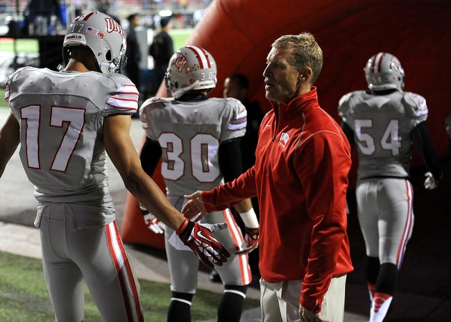 Nov 30, 2013; Las Vegas, NV, USA; UNLV Rebels head coach Bobby Hauck shakes hands with Rebel players as they prepare to take the field against the San Diego State Aztecs at Sam Boyd Stadium. Mandatory Credit: Stephen R. Sylvanie-USA TODAY Sports