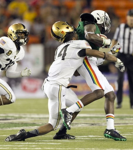 Nov 30, 2013; Honolulu, HI, USA; Army Black Knights defensive back Steven Johnson (14) loses his helmet as he tries to stop Hawaii Warriors wide receiver Chris Gant (9) during the third quarter at Aloha Stadium. Mandatory Credit: Marco Garcia-USA TODAY Sports
