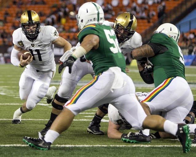 Nov 30, 2013; Honolulu, HI, USA; Army Black Knights quarterback A.J. Schurr (11)  runs against the Hawaii Warriors during the third quarter at Aloha Stadium. Mandatory Credit: Marco Garcia-USA TODAY Sports