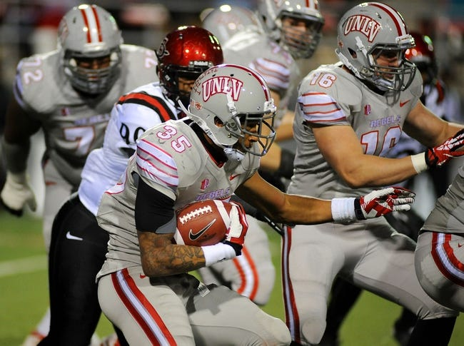 Nov 30, 2013; Las Vegas, NV, USA; UNLV Rebels running back Tim Cornett (35) carries the ball for a gain against the San Diego State Aztecs during an NCAA football game at Sam Boyd Stadium. UNLV won the game 45-19. Mandatory Credit: Stephen R. Sylvanie-USA TODAY Sports