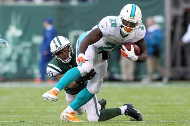 Dec 1, 2013; East Rutherford, NJ, USA; Miami Dolphins running back Lamar Miller (26) breaks a tackle by New York Jets corner back Dee Milliner (27) during the third quarter of a game at MetLife Stadium. The Dolphins defeated the Jets 23-3. Mandatory Credit: Brad Penner-USA TODAY Sports