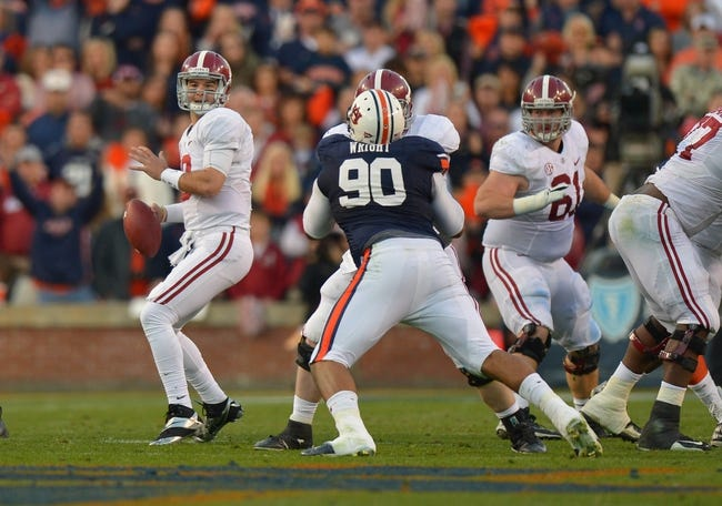 Nov 30, 2013; Auburn, AL, USA; Alabama Crimson Tide quarterback AJ McCarron (10) looks downfield as he is pressured by Auburn Tigers defensive lineman Gabe Wright (90) at Jordan Hare Stadium. Mandatory Credit: RVR Photos-USA TODAY Sports