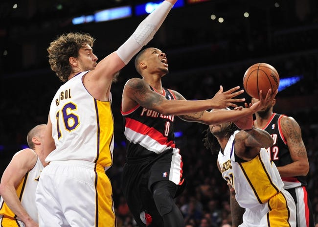 December 1, 2013; Los Angeles, CA, USA; Portland Trail Blazers point guard Damian Lillard (0) goes in for a basket against the Los Angeles Lakers center Pau Gasol (16) and center Jordan Hill (27) during the first half at Staples Center. Mandatory Credit: Gary A. Vasquez-USA TODAY Sports