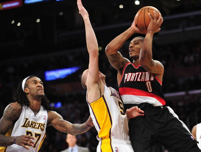 December 1, 2013; Los Angeles, CA, USA; Portland Trail Blazers point guard Damian Lillard (0) moves the ball against the defense of Los Angeles Lakers point guard Steve Blake (5) during the first half at Staples Center. Mandatory Credit: Gary A. Vasquez-USA TODAY Sports