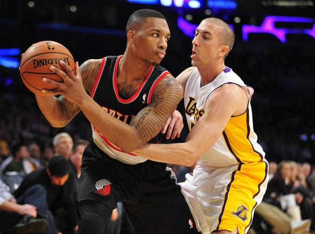 December 1, 2013; Los Angeles, CA, USA; Portland Trail Blazers point guard Damian Lillard (0) controls the ball against the defense of Los Angeles Lakers point guard Steve Blake (5) during the first half at Staples Center. Mandatory Credit: Gary A. Vasquez-USA TODAY Sports