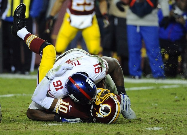 Dec 1, 2013; Landover, MD, USA; Washington Redskins quarterback Robert Griffin III (10) is sacked by New York Giants defensive end Justin Tuck (91) during the second half at FedEx Field. The Giants won 24 - 17. Mandatory Credit: Brad Mills-USA TODAY Sports