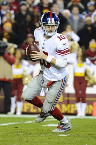 Dec 1, 2013; Landover, MD, USA; New York Giants quarterback Eli Manning (10) rolls out against the Washington Redskins during the first half at FedEx Field. Mandatory Credit: Brad Mills-USA TODAY Sports