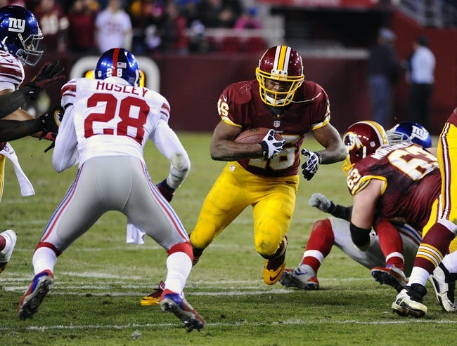 Dec 1, 2013; Landover, MD, USA; Washington Redskins running back Alfred Morris (46) runs the ball as New York Giants cornerback Jayron Hosley (28) defends during the second half at FedEx Field. The Giants won 24 - 17. Mandatory Credit: Brad Mills-USA TODAY Sports