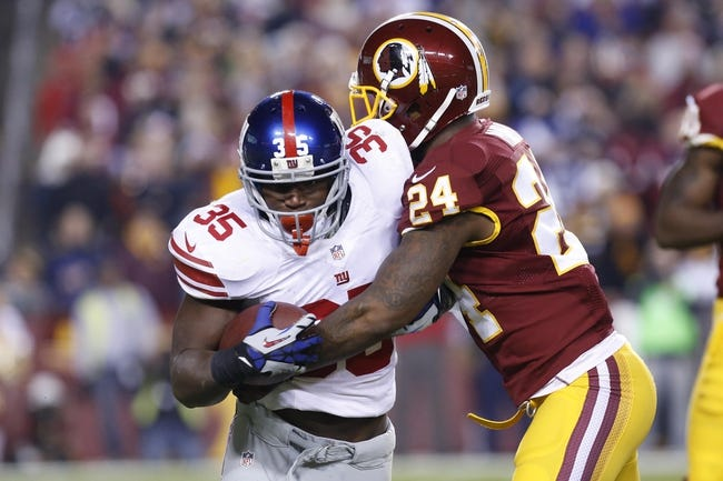 Dec 1, 2013; Landover, MD, USA; New York Giants running back Andre Brown (35) carries the ball as Washington Redskins strong safety Bacarri Rambo (24) attempts to tackle in the third quarter at FedEx Field. The Giants won 24-17. Mandatory Credit: Geoff Burke-USA TODAY Sports