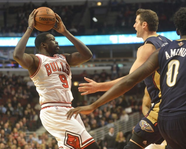 Dec 2, 2013; Chicago, IL, USA; Chicago Bulls small forward Luol Deng (9) passes away from New Orleans Pelicans center Jason Smith (14) during the first half of their game at the United Center.  Mandatory Credit: Matt Marton-USA TODAY Sports