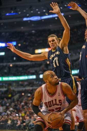 Dec 2, 2013; Chicago, IL, USA; Chicago Bulls power forward Taj Gibson (22) is blocked by New Orleans Pelicans power forward Lou Amundson (17) during the first half of their game at the United Center.  Mandatory Credit: Matt Marton-USA TODAY Sports