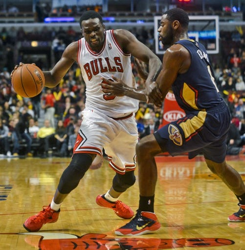 Dec 2, 2013; Chicago, IL, USA; Chicago Bulls small forward Luol Deng (9) drives past New Orleans Pelicans point guard Tyreke Evans (1) during the first half of their game at the United Center.  Mandatory Credit: Matt Marton-USA TODAY Sports