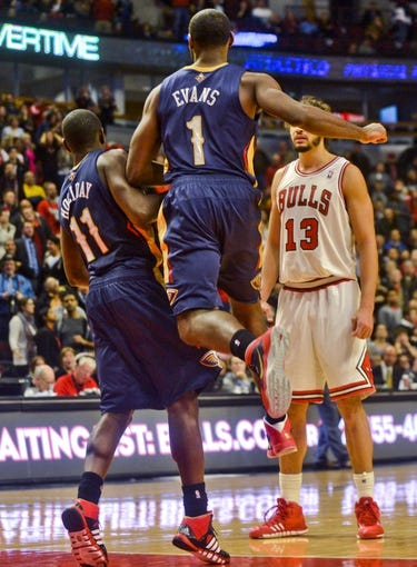 Dec 2, 2013; Chicago, IL, USA; New Orleans Pelicans point guard Jrue Holiday (11) and New Orleans Pelicans point guard Tyreke Evans (1) collide after Holiday scored the game winning basket during the third overtime of their game against the Chicago Bulls at the United Center.  Mandatory Credit: Matt Marton-USA TODAY Sports