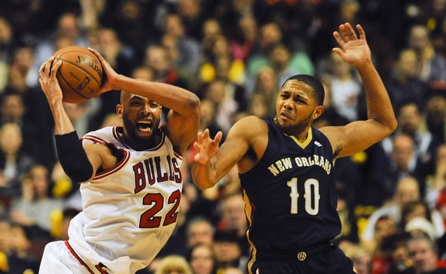 Dec 2, 2013; Chicago, IL, USA; Chicago Bulls power forward Taj Gibson (22) and New Orleans Pelicans shooting guard Eric Gordon (10) fight for a ball at the United Center. The Pelicans beat the Bulls 131-128.  Mandatory Credit: Matt Marton-USA TODAY Sports