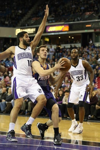 Nov 19, 2013; Sacramento, CA, USA; Phoenix Suns shooting guard Goran Dragic (1) drives in between Sacramento Kings point guard Greivis Vasquez (10) and power forward Luc Richard Mbah a Moute (33) during the first quarter at Sleep Train Arena. Mandatory Credit: Kelley L Cox-USA TODAY Sports