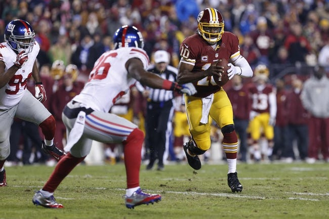 Dec 1, 2013; Landover, MD, USA; Washington Redskins quarterback Robert Griffin III (10) runs with the ball as New York Giants strong safety Antrel Rolle (26) chases in the third quarter at FedEx Field. The Giants won 24-17. Mandatory Credit: Geoff Burke-USA TODAY Sports