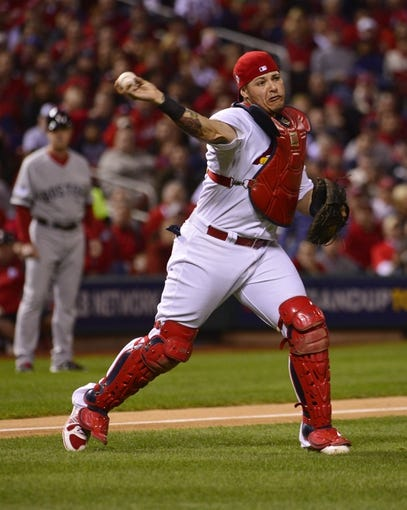 Oct 28, 2013; St. Louis, MO, USA; St. Louis Cardinals catcher Yadier Molina throws to first base against the Boston Red Sox in the second inning during game five of the MLB baseball World Series at Busch Stadium. Mandatory Credit: Scott Rovak-USA TODAY Sports