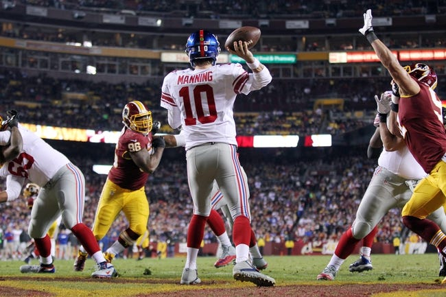 Dec 1, 2013; Landover, MD, USA; New York Giants quarterback Eli Manning (10) throws the ball as Washington Redskins outside linebacker Ryan Kerrigan (91) and Redskins nose tackle Barry Cofield (96) chase in the third quarter at FedEx Field. The Giants won 24-17. Mandatory Credit: Geoff Burke-USA TODAY Sports