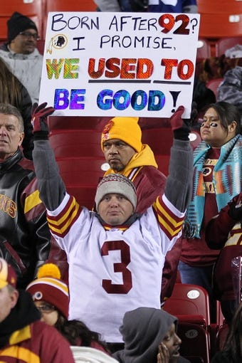 Dec 1, 2013; Landover, MD, USA; A Washington Redskins fan holds a sign after the game against the New York Giants at FedEx Field. The Giants won 24-17. Mandatory Credit: Geoff Burke-USA TODAY Sports