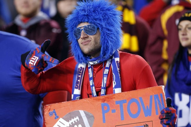 Dec 1, 2013; Landover, MD, USA; A New York Giants fan cheers in the stands against the Washington Redskins in the fourth quarter at FedEx Field. The Giants won 24-17. Mandatory Credit: Geoff Burke-USA TODAY Sports