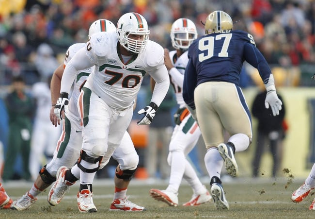 Nov 29, 2013; Pittsburgh, PA, USA; Miami Hurricanes offensive linesman Jon Feliciano (70) blocks at the line of scrimmage against Pittsburgh Panthers defensive lineman Aaron Donald (97) during the first quarter at Heinz Field. Miami won 41-31. Mandatory Credit: Charles LeClaire-USA TODAY Sports