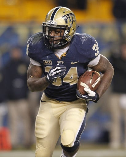 Nov 29, 2013; Pittsburgh, PA, USA; Pittsburgh Panthers running back Isaac Bennett (34) carries the ball against the Miami Hurricanes during the third quarter at Heinz Field. Miami won 41-31. Mandatory Credit: Charles LeClaire-USA TODAY Sports