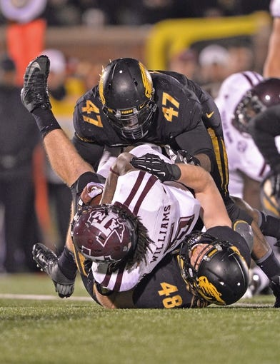 Nov 30, 2013; Columbia, MO, USA; Missouri Tigers defenders Andrew Wilson (48) and Kony Ealy (47) tackle Texas A&M Aggies running back Brandon Williams (5) for a loss during the second half at Faurot Field. Mandatory Credit: Peter G. Aiken-USA TODAY Sports
