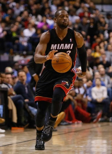 Nov 29, 2013; Toronto, Ontario, CAN; Miami Heat guard Dwyane Wade (3) carries the ball against the Toronto Raptors at the Air Canada Centre. Miami defeated Toronto 90-83. Mandatory Credit: John E. Sokolowski-USA TODAY Sports