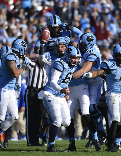 Nov 30, 2013; Chapel Hill, NC, USA; North Carolina Tar Heels safety Brandon Ellerbe (20) and wide receiver Mack Hollins (13) and long snapper Conor Fry (61) and defensive lineman Allen Champagne (91) react after Hollins fumble recovery in the second quarter at Kenan Memorial Stadium. Mandatory Credit: Bob Donnan-USA TODAY Sports