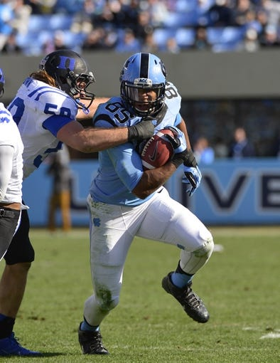 Nov 30, 2013; Chapel Hill, NC, USA; North Carolina Tar Heels tight end Eric Ebron (85) with the ball as Duke Blue Devils defensive end Michael Mann (58) defends in the second quarter at Kenan Memorial Stadium. Mandatory Credit: Bob Donnan-USA TODAY Sports