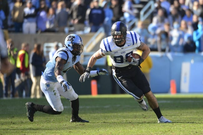 Nov 30, 2013; Chapel Hill, NC, USA;  Duke Blue Devils tight end Braxton Deaver (89) with the ball as North Carolina Tar Heels cornerback Jabari Price (4) defends in the third quarter. The Blue Devils defeated the Tar Heels 27-25 at Kenan Memorial Stadium. Mandatory Credit: Bob Donnan-USA TODAY Sports