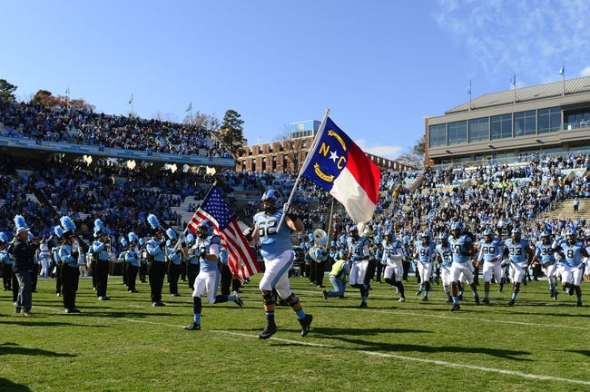 Nov 30, 2013; Chapel Hill, NC, USA;  North Carolina Tar Heels defensive back Joshua Broach (38) and guard David Collins (62) carry the flags as the Tar Heels run on to the field at Kenan Memorial Stadium. Mandatory Credit: Bob Donnan-USA TODAY Sports