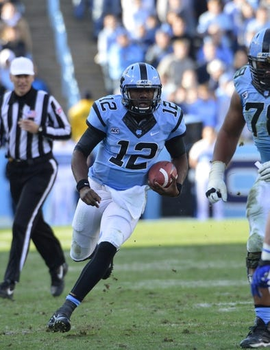 Nov 30, 2013; Chapel Hill, NC, USA; North Carolina Tar Heels quarterback Marquise Williams (12) runs in the fourth quarter. The Blue Devils defeated the Tar Heels 27-25 at Kenan Memorial Stadium. Mandatory Credit: Bob Donnan-USA TODAY Sports