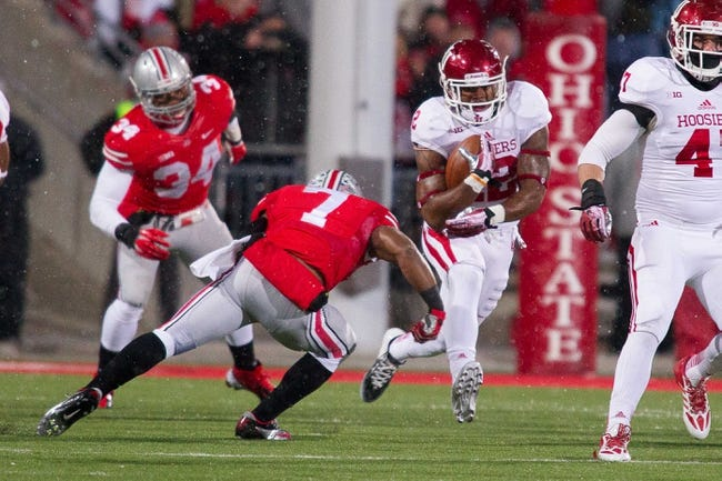 Nov 23, 2013; Columbus, OH, USA;  Indiana Hoosiers running back Stephen Houston (12) runs the ball and is tackled by Ohio State Buckeyes running back Jordan Hall (7) in the second quarter of the game at Ohio Stadium. Ohio State Buckeyes beat Indiana Hoosiers 42-14. Mandatory Credit: Trevor Ruszkowksi-USA TODAY Sports