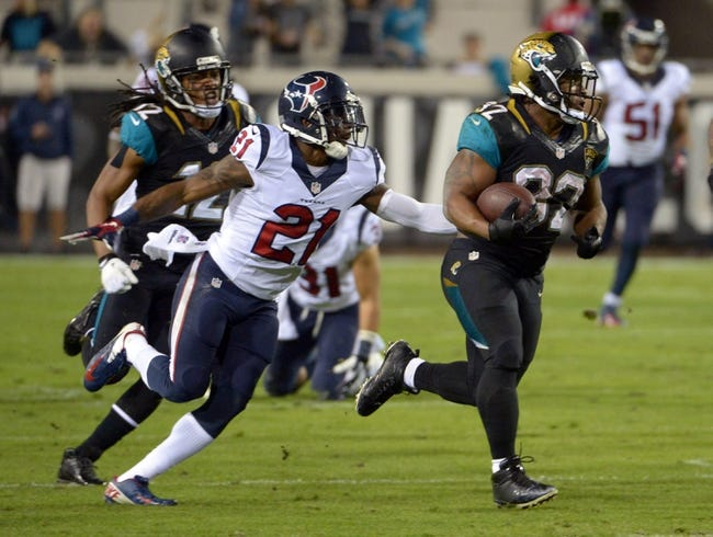 Dec 5, 2013; Jacksonville, FL, USA; Jacksonville Jaguars running back Maurice Jones-Drew (32) is pursued by Houston Texans cornerback Brice McCain (21) at EverBank Field. The Jaguars defeated the Texans 27-20.  Mandatory Credit: Kirby Lee-USA TODAY Sports