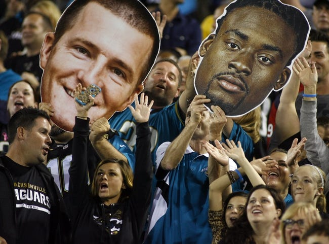 Dec 5, 2013; Jacksonville, FL, USA; Jacksonville Jaguars fans hold up headshots of Jacksonville Jaguars kicker Josh Scobee (not pictured) and safety Johnathan Cyprien (not pictured) in the fourth quarter at EverBank Field. The Jacksonville Jaguars best the Houston Texans 27-20. Mandatory Credit: Phil Sears-USA TODAY Sports