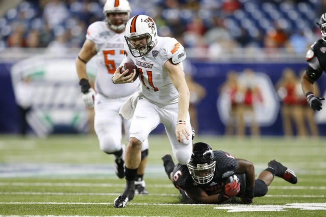 Dec 6, 2013; Detroit, MI, USA; Bowling Green Falcons quarterback Matt Johnson (11) breaks a tackle by Northern Illinois Huskies linebacker Jamaal Bass (6) in the third quarter at Ford Field. Bowling Green won 47-27. Mandatory Credit: Rick Osentoski-USA TODAY Sports