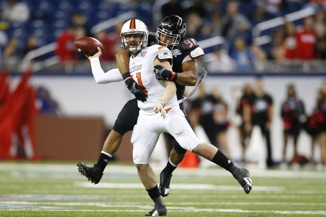 Dec 6, 2013; Detroit, MI, USA; Bowling Green Falcons quarterback Matt Johnson (11) is tackled by Northern Illinois Huskies defensive end Joe Windsor (97) in the fourth quarter at Ford Field. Bowling Green won 47-27. Mandatory Credit: Rick Osentoski-USA TODAY Sports