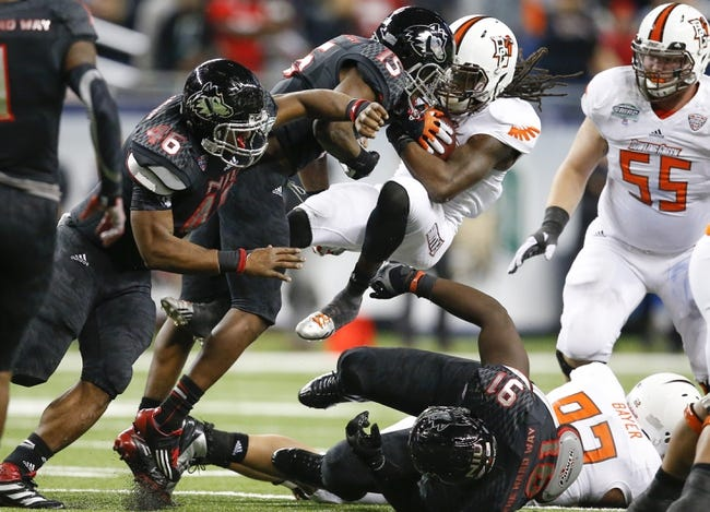 Dec 6, 2013; Detroit, MI, USA; Bowling Green Falcons running back Travis Greene (13) is tackled by Northern Illinois Huskies safety Jimmie Ward (15) in the third quarter at Ford Field. Bowling Green won 47-27. Mandatory Credit: Rick Osentoski-USA TODAY Sports