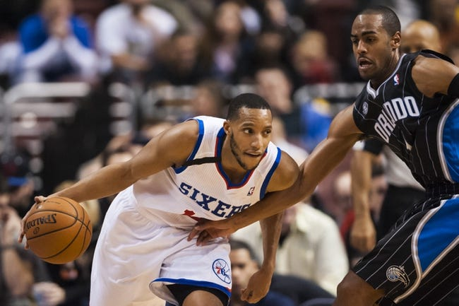 Dec 3, 2013; Philadelphia, PA, USA; Philadelphia 76ers guard Evan Turner (12) is defended by Orlando Magic guard Arron Afflalo (4) during the third quarter at the Wells Fargo Center. The Sixers defeated the Magic 126-125 in double overtime. Mandatory Credit: Howard Smith-USA TODAY Sports