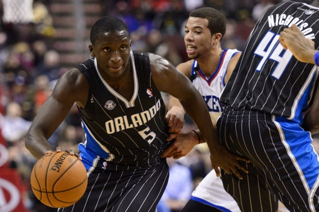 Dec 3, 2013; Philadelphia, PA, USA; Orlando Magic guard Victor Oladipo (5) goes around the pick set by forward Andrew Nicholson (44) as Philadelphia 76ers guard Michael Carter-Williams (1) defends during the third quarter at the Wells Fargo Center. The Sixers defeated the Magic 126-125 in double overtime. Mandatory Credit: Howard Smith-USA TODAY Sports