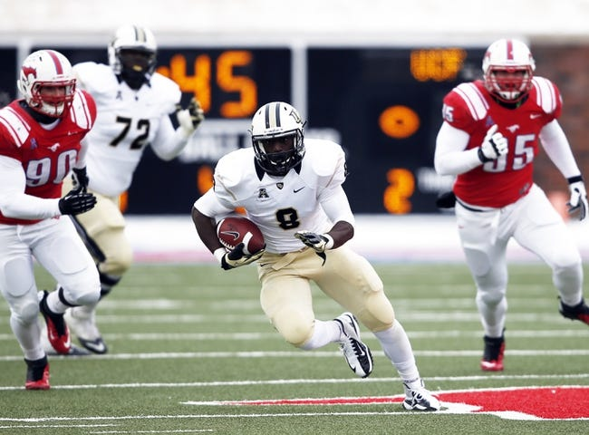 Dec 7, 2013; Dallas, TX, USA; UCF Knights running back Storm Johnson (8) rushes against Southern Methodist Mustangs defensive end Zach Wood (90) and defensive lineman Andrew McCleneghen (95) during the first half of an NCAA football game at Gerald J. Ford Stadium. Mandatory Credit: Jim Cowsert-USA TODAY Sports