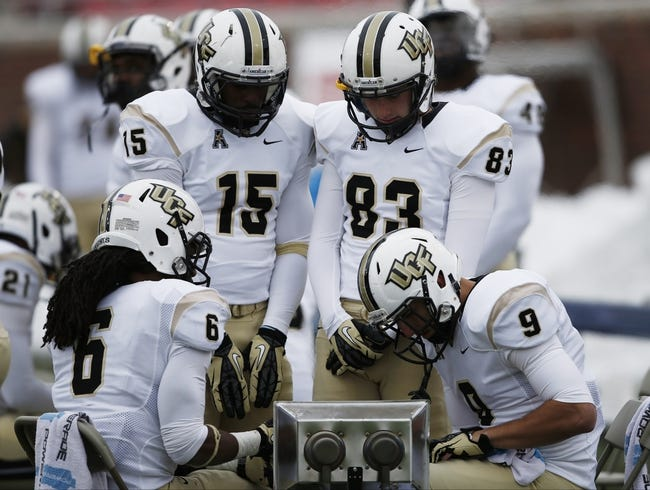 Dec 7, 2013; Dallas, TX, USA; UCF Knights wide receiver Rannell Hall (6), linebacker Michael Easton (15), kicker Shawn Moffitt (83) and wide receiver J.J. Worton (9) gather around a portable heater during the first half of an NCAA football game against the Southern Methodist Mustangs at Gerald J. Ford Stadium. Mandatory Credit: Jim Cowsert-USA TODAY Sports