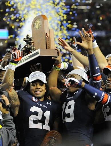 Dec 7, 2013; Atlanta, GA, USA; Auburn Tigers running back Tre Mason (21) celebrates after defeating the Missouri Tigers in the 2013 SEC Championship game at Georgia Dome. Auburn defeated Missouri 59-42. Mandatory Credit: Dale Zanine-USA TODAY Sports