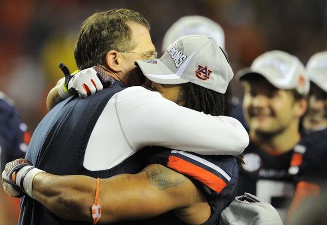 Dec 7, 2013; Atlanta, GA, USA; Auburn Tigers head coach Gus Malzahn (left) hugs Tre Mason (21) following their win over the Missouri Tigers in the 2013 SEC Championship game at Georgia Dome. Auburn defeated Missouri 59-42. Mason was named the game's most valuable player rushing for 304 yards. Mandatory Credit: Dale Zanine-USA TODAY Sports