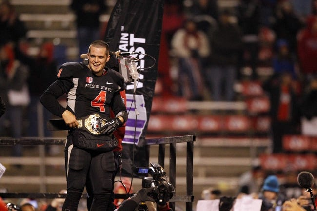 Dec 7, 2013; Fresno, CA, USA; Fresno State Bulldogs quarterback Derek Carr (4) puts on a Bulldogs belt in front of fans after the Bulldogs defeated the Utah State Aggies 24-17 at Bulldog Stadium. Mandatory Credit: Cary Edmondson-USA TODAY Sports