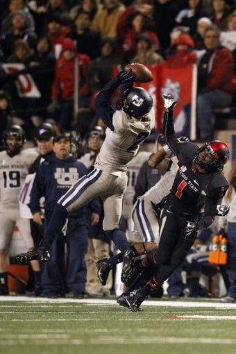 Dec 7, 2013; Fresno, CA, USA; Utah State Aggies safety Brian Suite (21) intercepts a pass intended for Fresno State Bulldogs wide receiver Isaiah Burse (1) in the third quarter at Bulldog Stadium. The Bulldogs defeated the Aggies 24-17. Mandatory Credit: Cary Edmondson-USA TODAY Sports